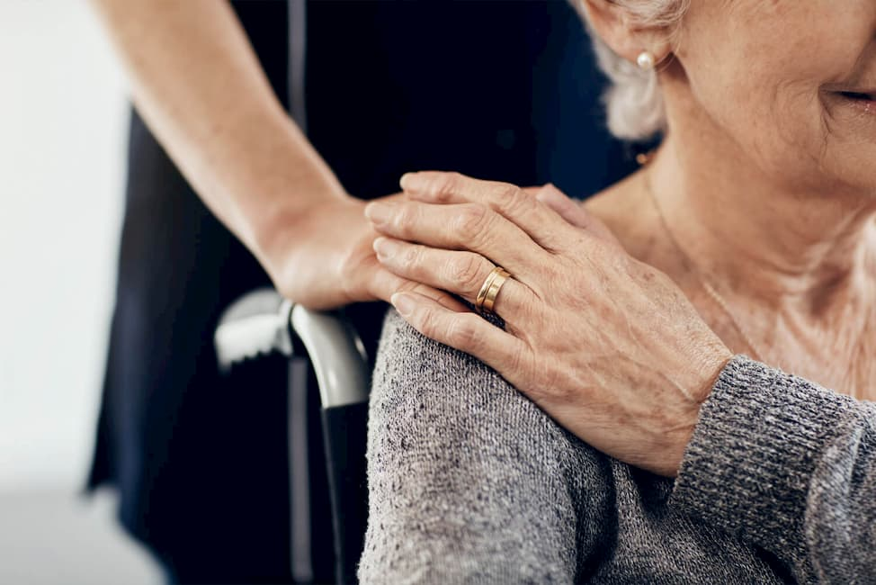 someone placing a hand on an elderly woman's shoulder that is sitting in a wheelchair