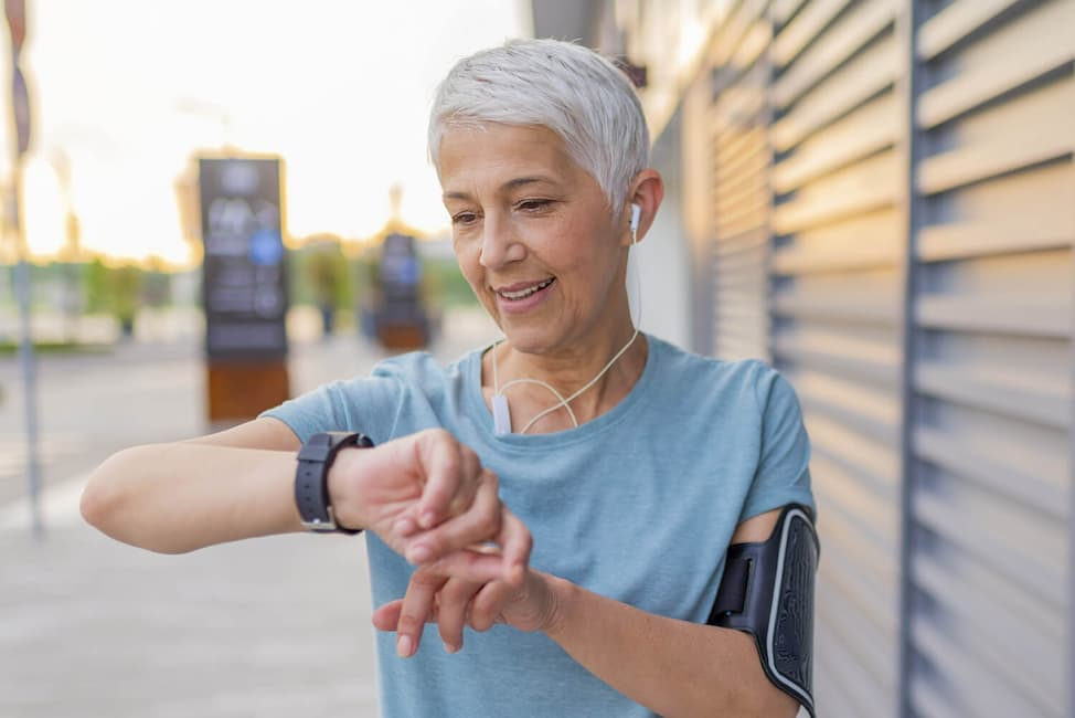 older woman outside with earbuds checking her watch