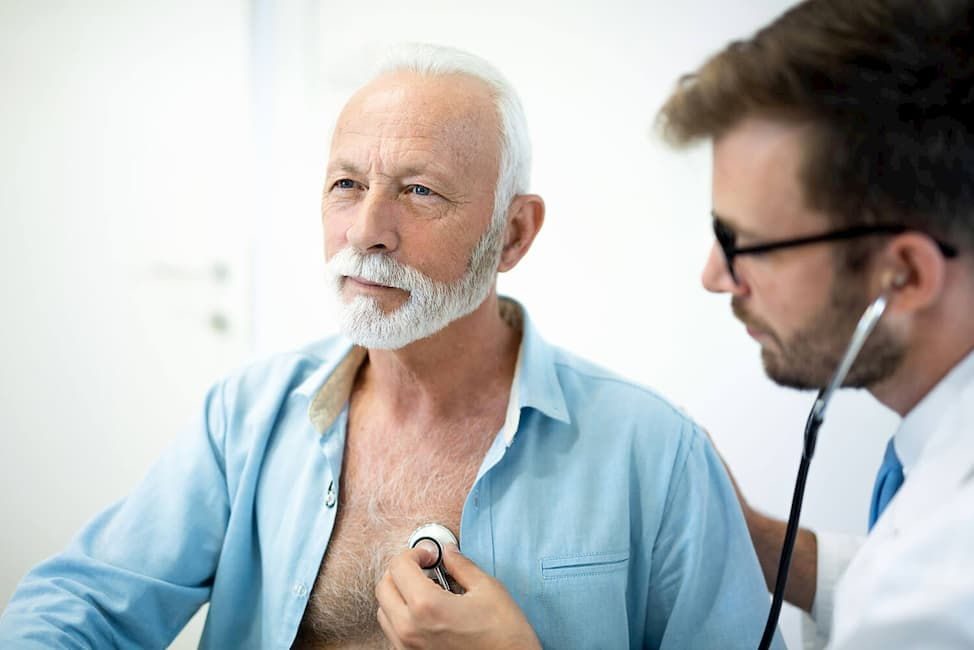 elderly man getting checked by a doctor using a stethoscope