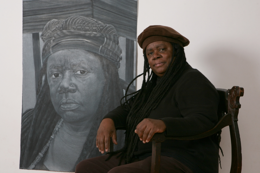 Diane Edison seated in front of her 2010 Self-Portrait drawing