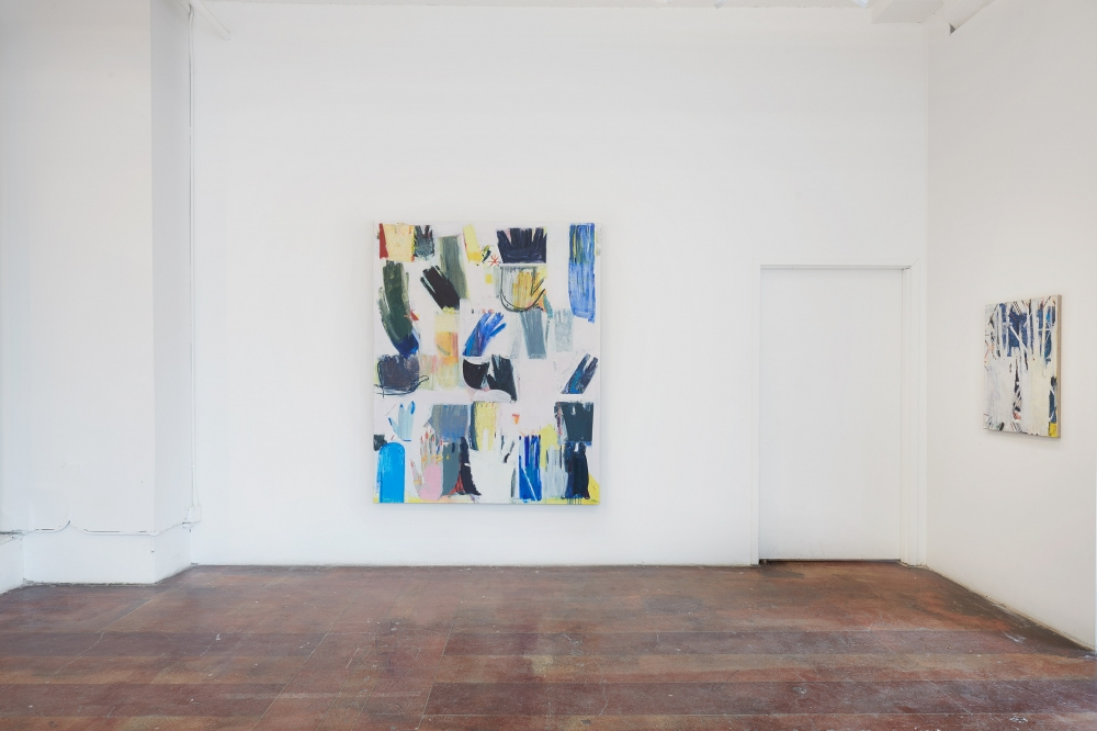 Installation image of the gallery- an oil painting of various sizes and colors of hands is prominently displayed