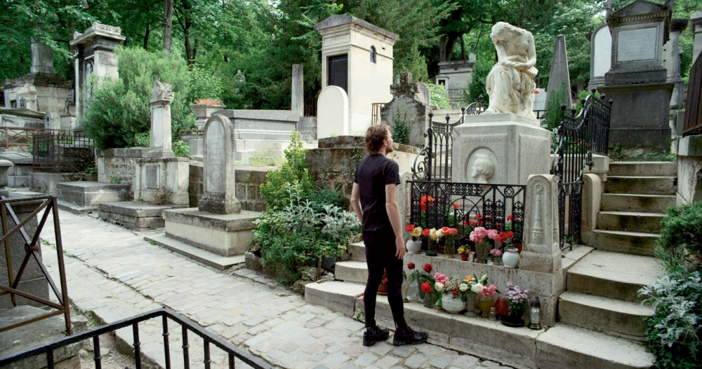 Man standing in front of grave