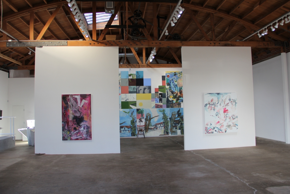 Image of interior DENK Gallery. At left, work from Iva Gueorguieva, pink, vertical, collage, in center, multiple colorful canvases by Frank J Stockton and on right works by Elisa Johns, mountains cape with pink
