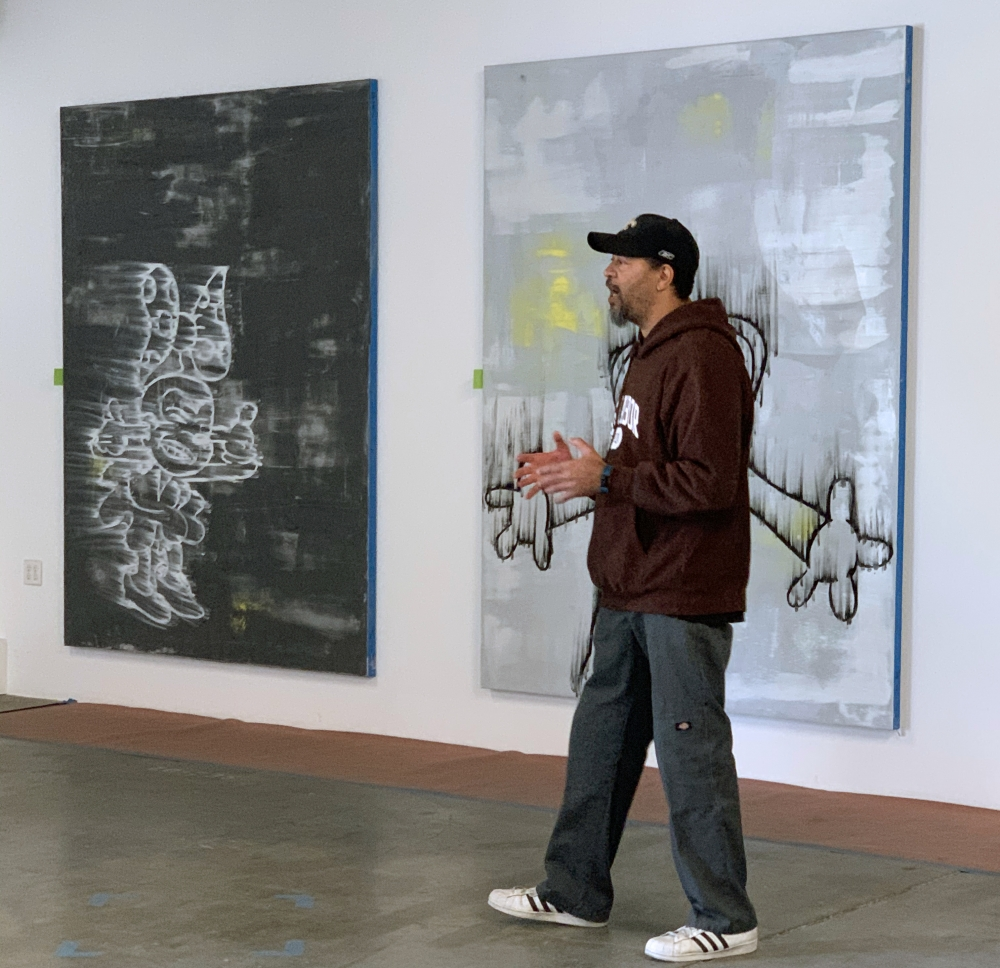 Portrait of the artist Gary Simmons in front of two paintings