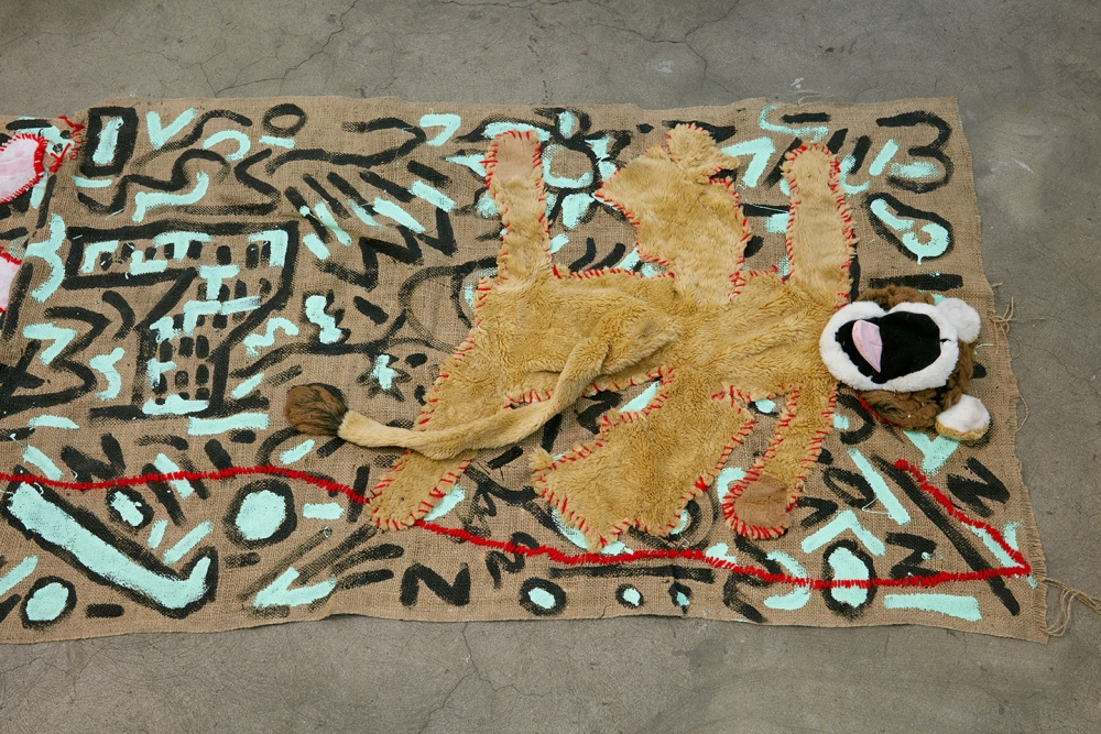 "Alex Chaves, ""Amerikan Green Cross Rug,"" 2015. Burlap, house paint, yarn, stuffed animals."