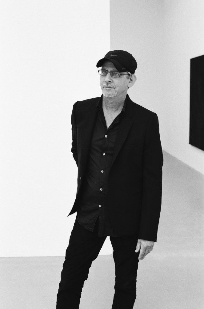black and white portrait of Troy Brauntuch standing and wearing a baseball cap