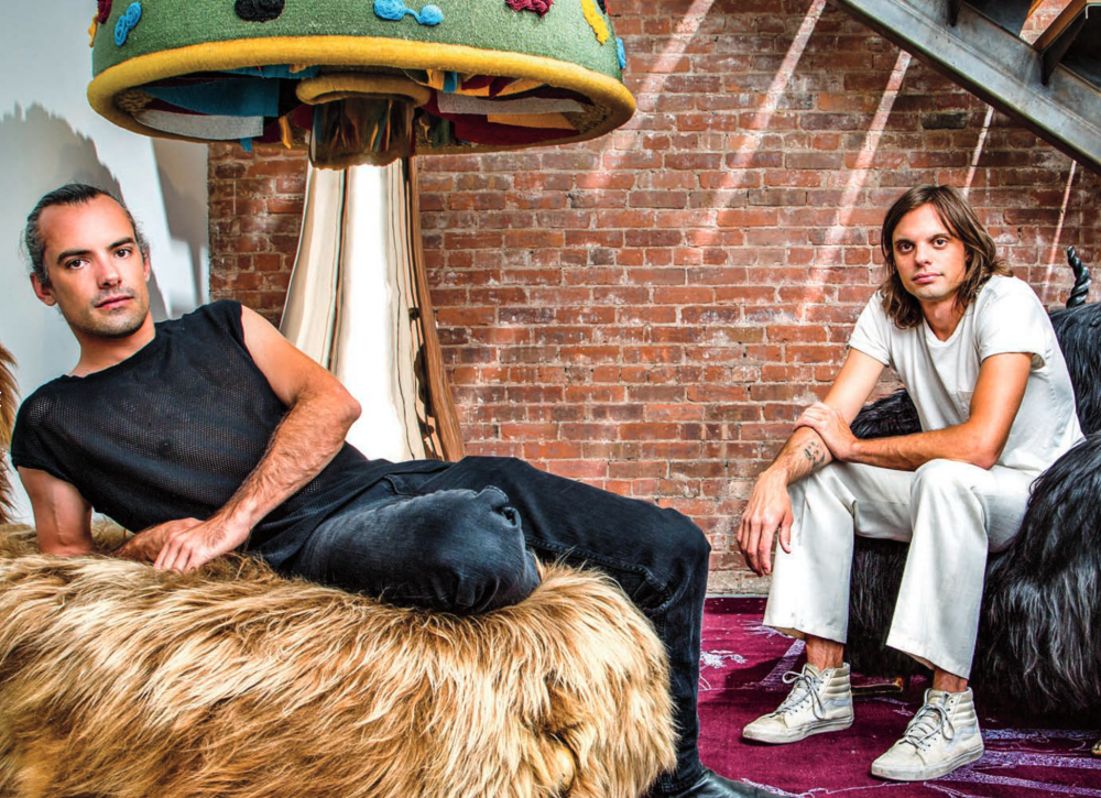 The Haas Brothers sitting on furry chairs with a mushroom sculpture they made