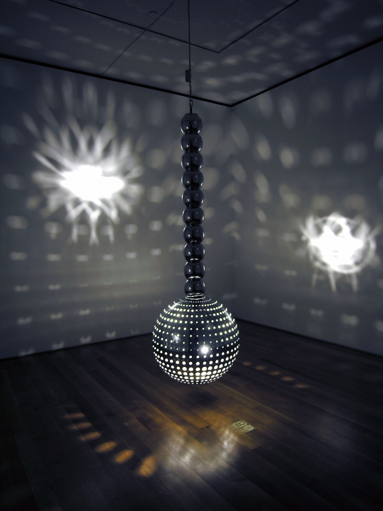 light sculpture suspended from the ceiling in a darkened gallery