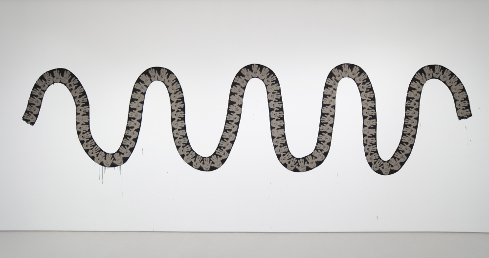 horizontal black serpentine line painted on a wall with mud handprints placed on top of the black line