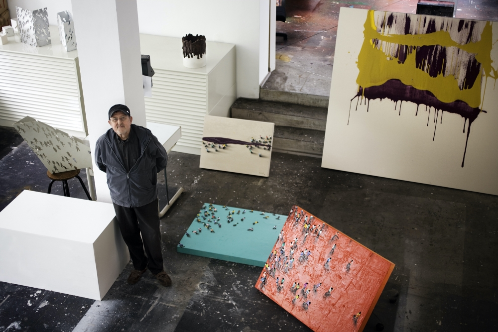 Color photographic portrait of Juan Genovés in his studio surrounded by paintings