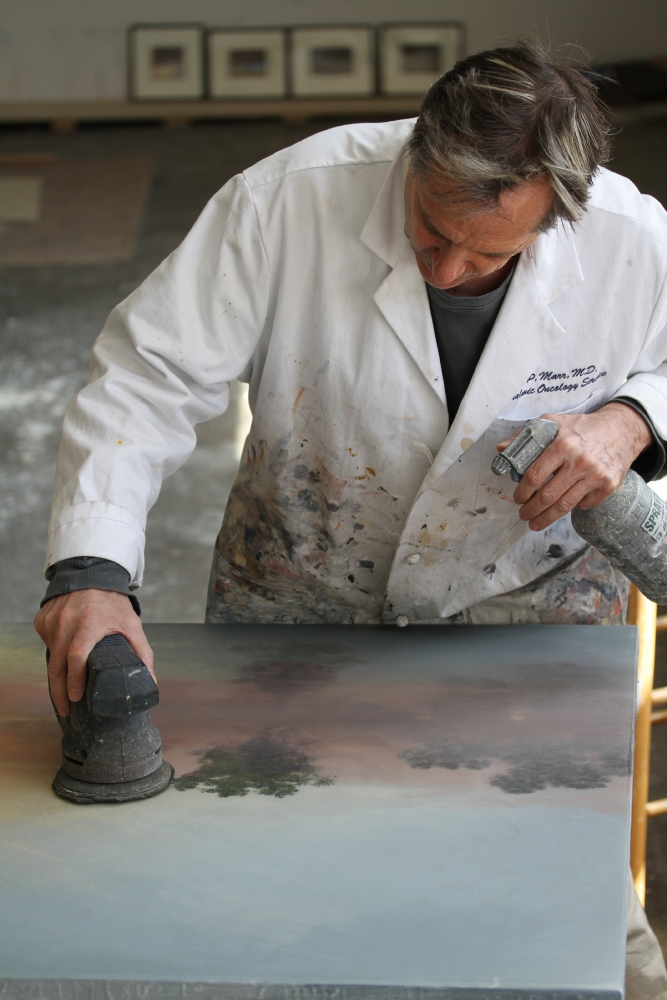 Color photograph of Stephen Hannock working on a painting.