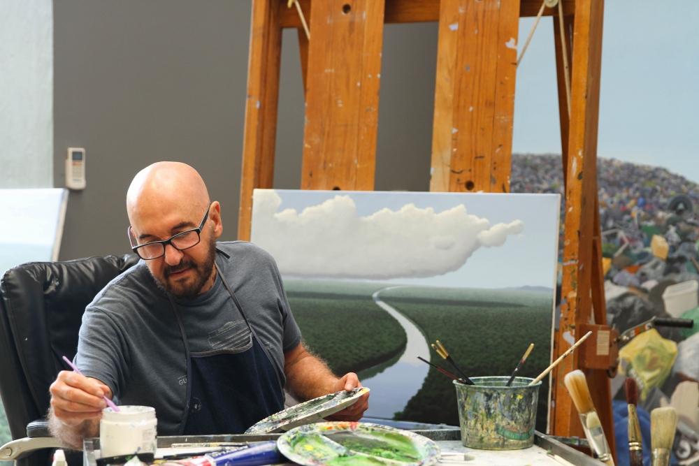 Color photographic portrait of Tomás Sánchez painting a river scene in his studio