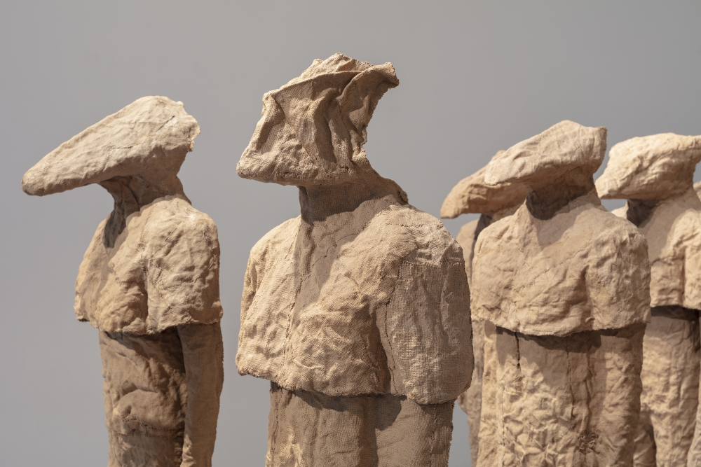 Detail view of multiple burlap and resin figures with different heads by Magdalena Abakanowicz