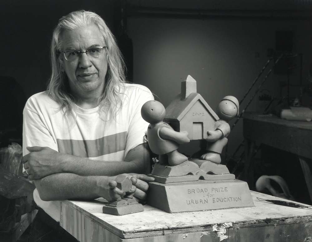 Black and white photographic portrait of Tom Otterness in his studio with model for Broad Prize for Urban Education
