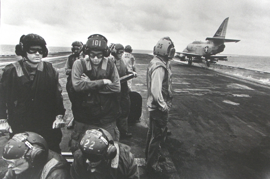 Philip Jones Griffiths - Bomb-laden planes are catapulted off the deck. Intended for emergency use in far-off conflicts, carriers are wasteful of men and machines, 1971 - Howard Greenberg Gallery