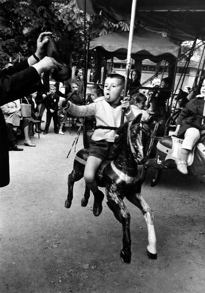 Alfred Eisenstaedt - Boy with tongue out spearing brass ring, Luxumbourg Garden, Paris, 1964 - Howard Greenberg Gallery