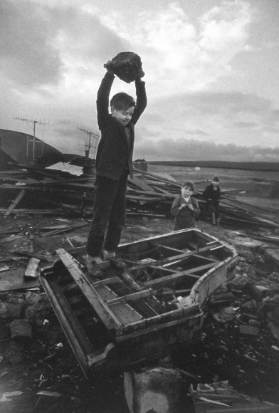 Philip Jones Griffiths - Boy Destroying Piano, Wales, 1961 - Howard Greenberg Gallery