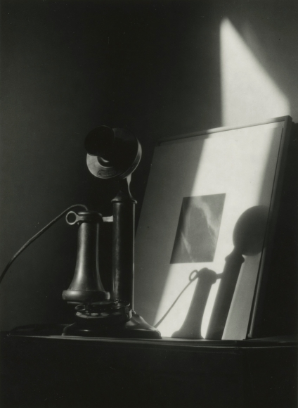 "Dorothy Norman - Telephone, in front of Alfred Stieglitz ""Equivalent,"" at An American Place, New York, c. 1940 - Howard Greenberg Gallery"