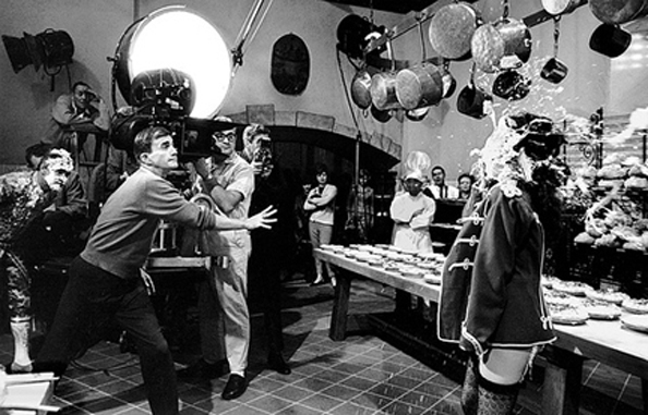 Blake Edwards throwing a pie at Natalie Wood on the set of The Great Race, Warner Bros. Studio, Burbank, California, 1964