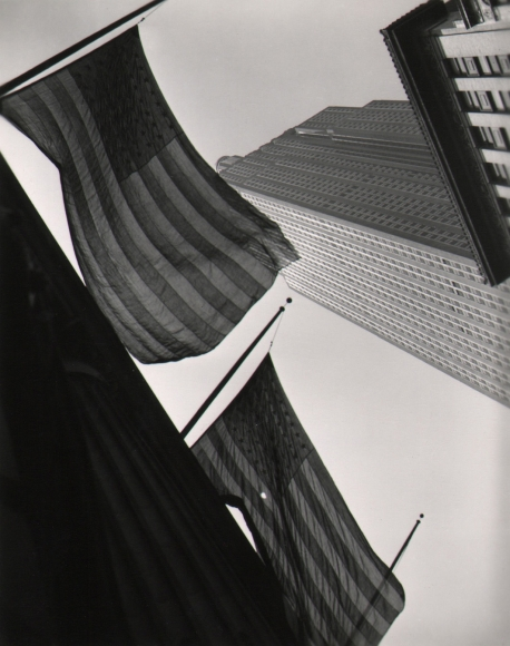 27. John C. Hatlem, Empire State Building, c. 1935. Street-level view looking up at the base of the Empire State Building, The view is partially obscured by two American flags hanging from the building nearest the photographer.