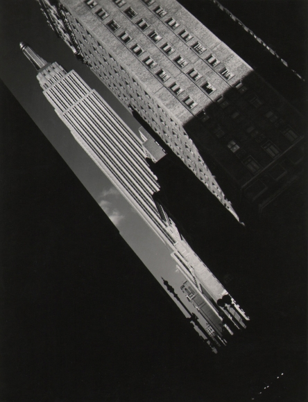 26. John C. Hatlem, Empire State Building, c. 1935. Street view tilted diagonally left showing the Empire State Building between other buildings cast in dark shadows.