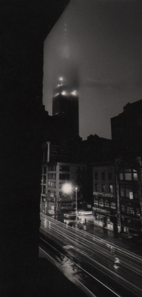 30. W. Eugene Smith, As From My Window I Sometimes Glance, 1957–1958. Nighttime view of a city street. The Empire State building is in the center background shrouded in fog.