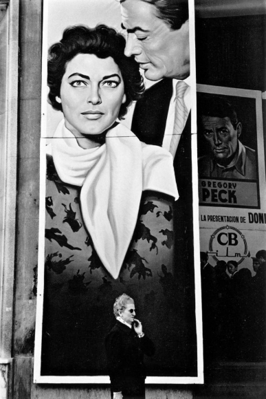 Woman in Front of Movie Poster, Seville, Spain, 1960 	Gelatin silver print mounted to board, printed later 	13 1/4 x 9 inches