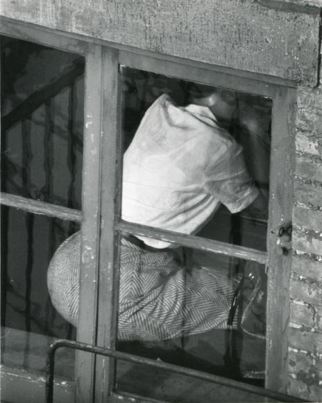 André Kertész - Portrait of a Woman in herring bone skirt in window, November 10, 1961 | Bruce Silverstein Gallery