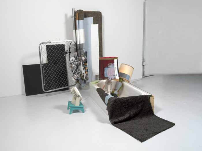 Jessica Stockholder, 2000, 2000, couch, photographs, metal gate, plywood, two lamps, bathtub, fish tank, fan, stool, embroidery thread, fake fur, extension cord, metal, acrylic paint, and metal bracket, 82 ½ × 84 × 128 in.