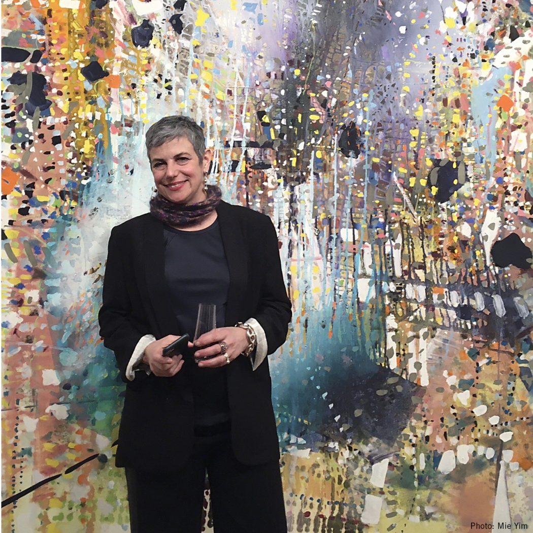 picture of Jackie Saccoccio standing in front of one of her multi-colored abstract paintings