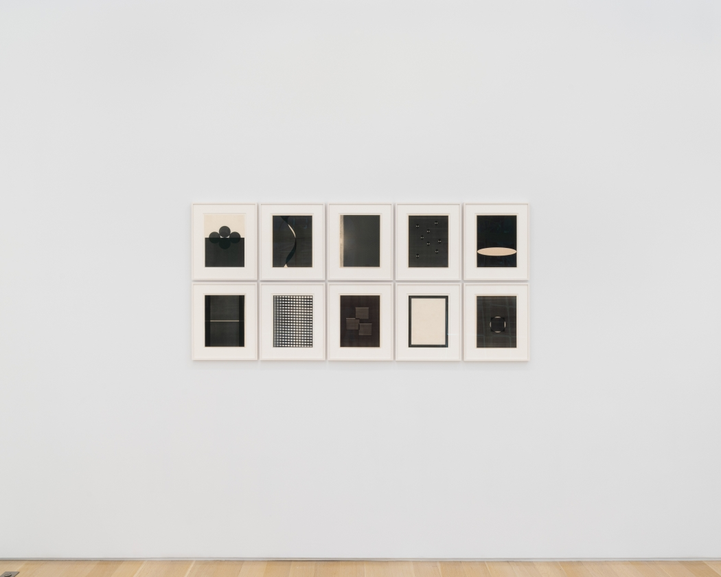 a group of ten framed works  on a white wall