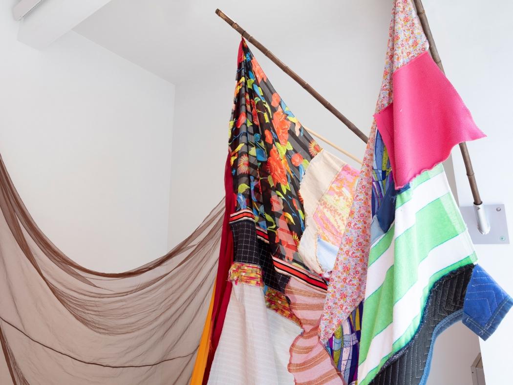 "Detail of Eric N. Mack's ""Landlord"", 2021 umbrella, wood flagpoles, metal brackets, fabric collage, thread dimensions variable"