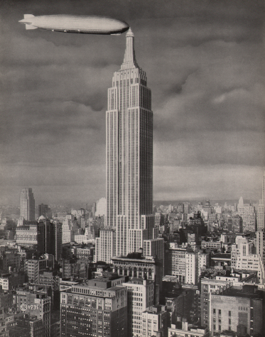 City skyline with the towering Empire State Building in center frame. A dirigible is docked on the left at the highest point of the building.