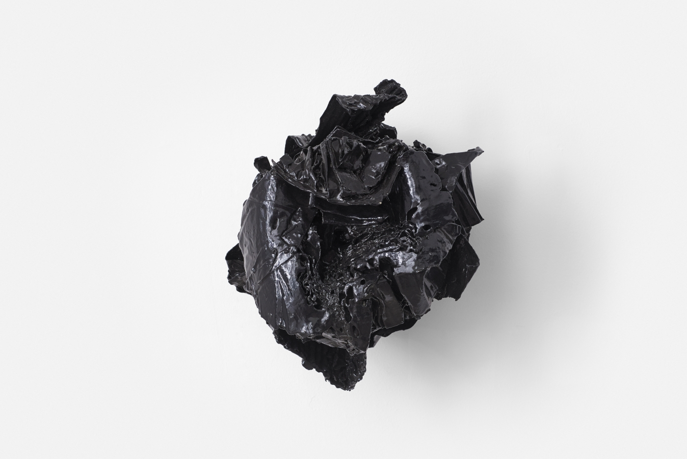 an abstract black sculpture hangs on the wall
