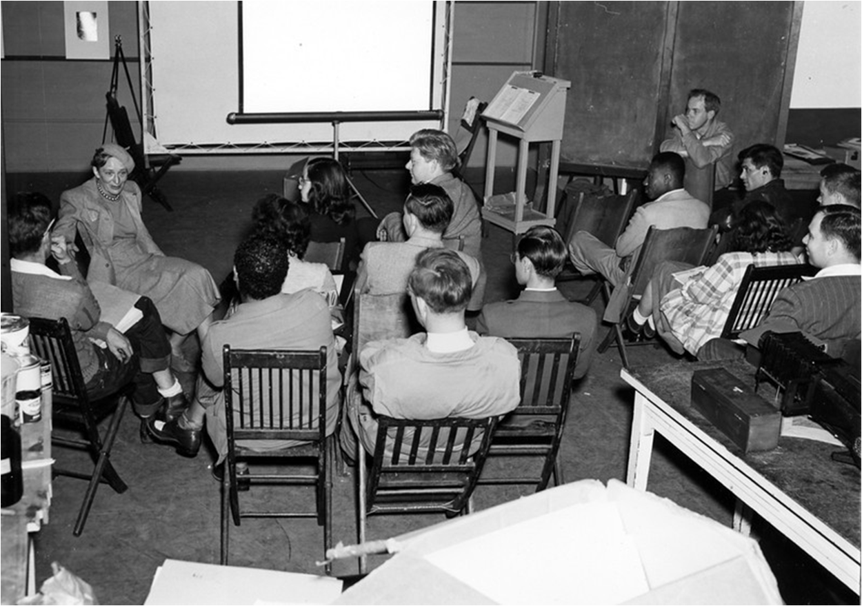 Instructor Dorothea Lange lecturing students in Studio 18; photography department chair Minor White looks on, back right, 1947.