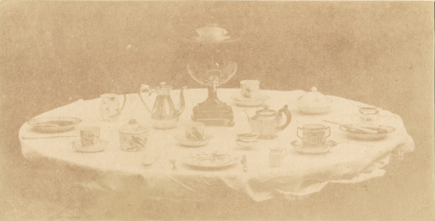 """William Henry Fox TALBOT (English, 1800-1877) Table set for tea, 1841-1842 Varnished salt print from a calotype negative 8.5 x 16.8 cm mounted on card, ruled  """"Patent Talbotype Photogenic Drawing"""" label on mount verso"""
