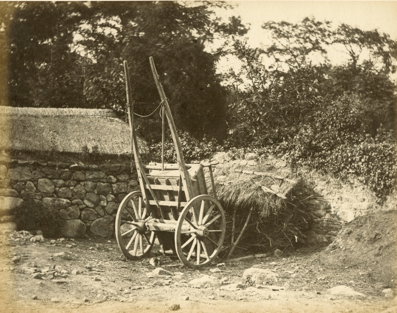 """Hugh OWEN (English, 1808-1897) Cart and thatched kindling storehouse Albumen print, 1860s-1870s, from a paper negative, before 1855 17.6 x 22.5 cm mounted on 26.0 x 28.3 cm album sheet Numbered """"36"""" in pencil on mount"""