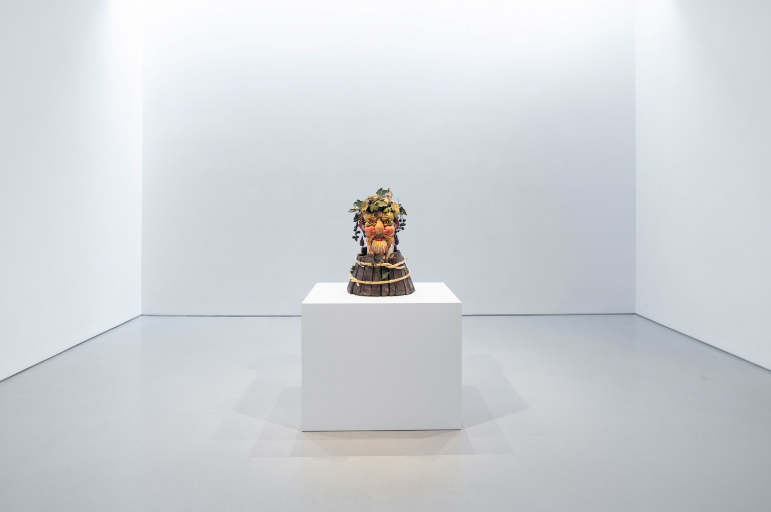 a bust of fruits and vegetables sits on a white pedestal in a big gallery room