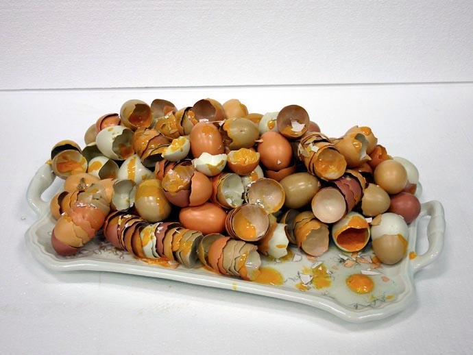 white ceramic tray with two handles holding a large number of broken eggshells
