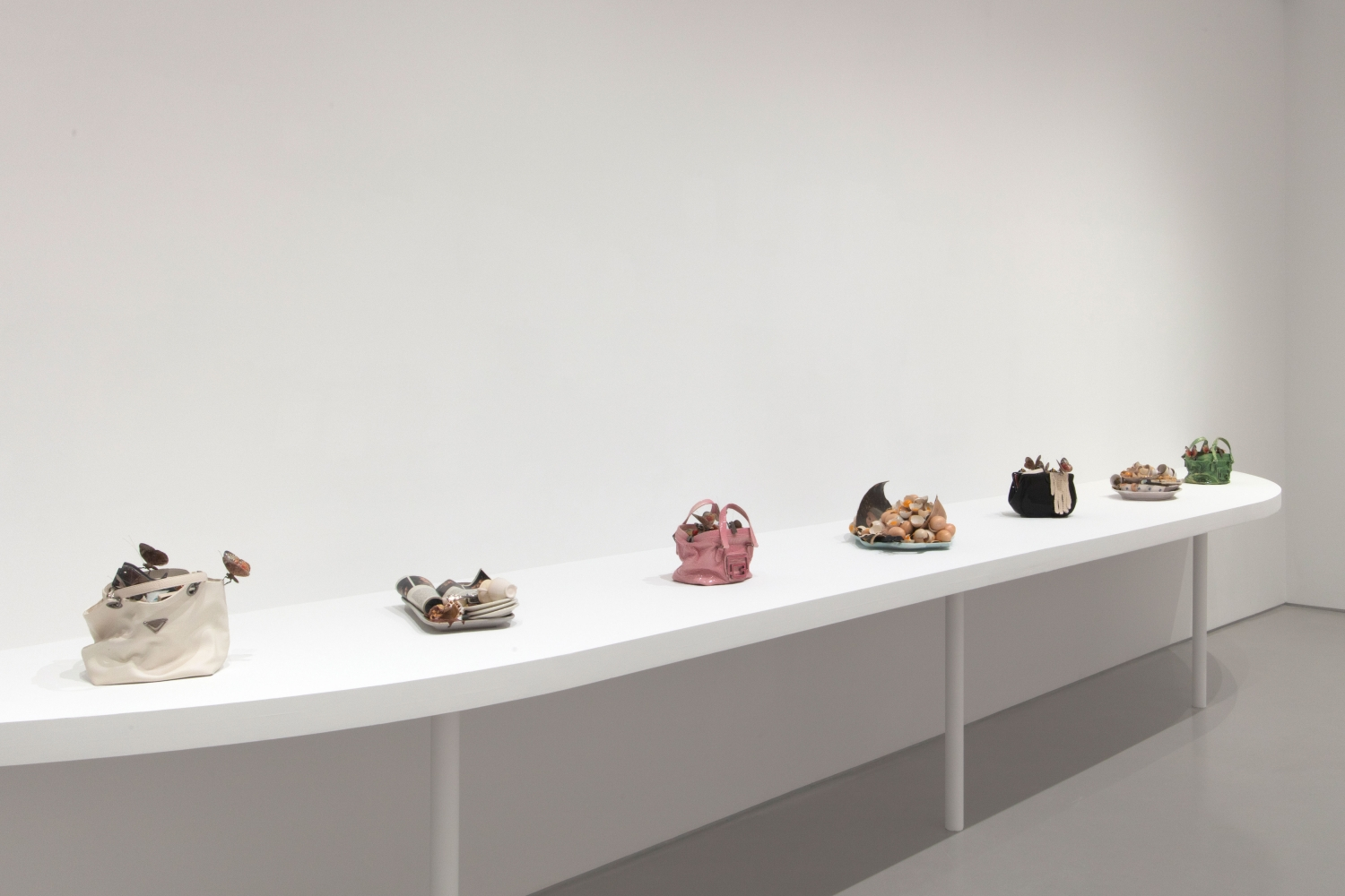 a white shelf holds seven sculptures resembling designer handbags and food trays
