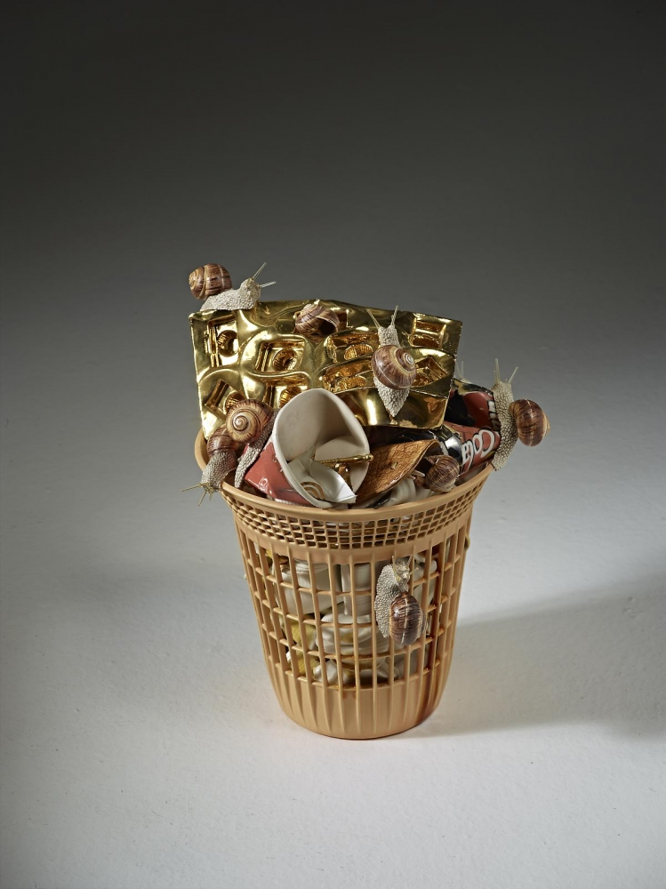 ceramic basket filled with cups and trash with snails