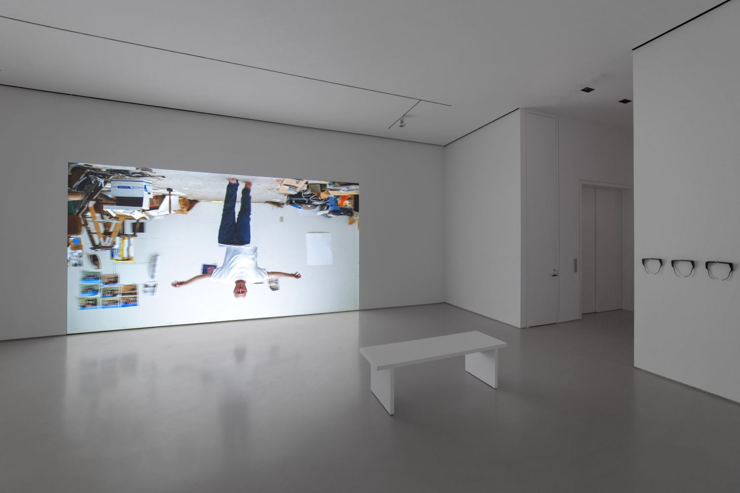 gallery installation view showing a projection of an upside down man walking with arms outstretched