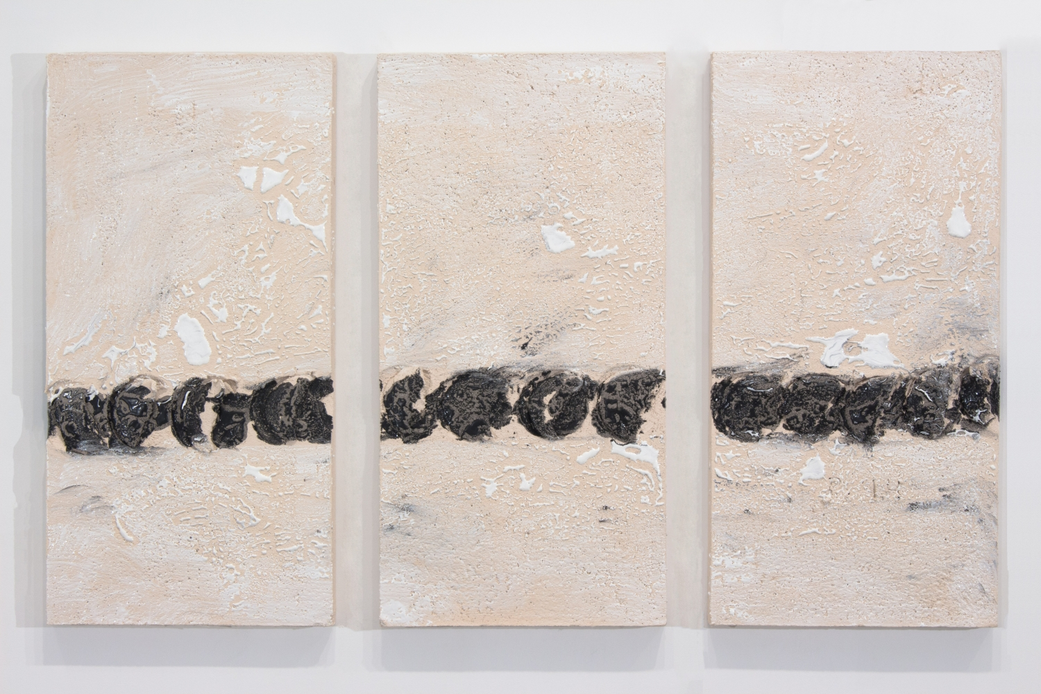 triptych of white ceramic panels with a line of black circular gouges across the lower half of each panel