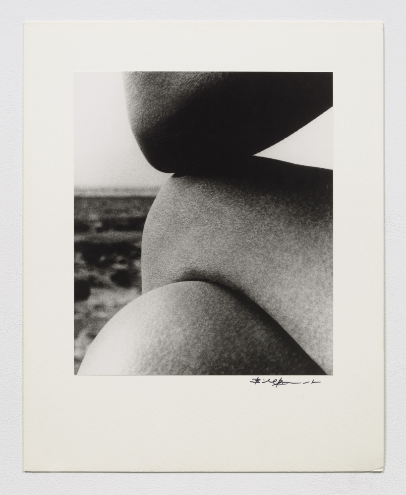 Black and white silver gelatin print of crossed knees and elbows with landscape in background.