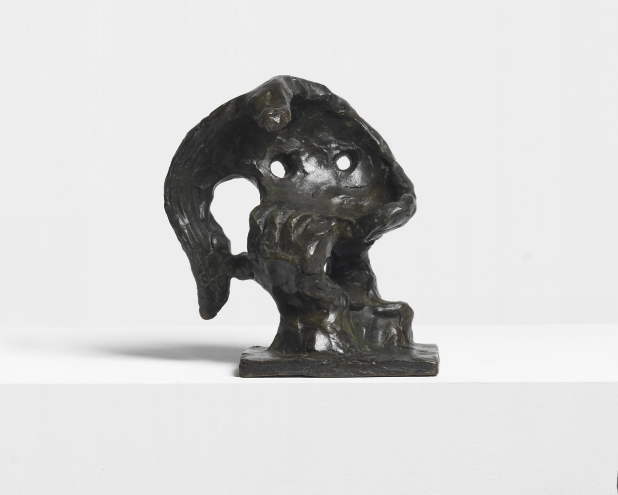 Abstract bronze sculpture depicting the head of a woman, hair, and hand.