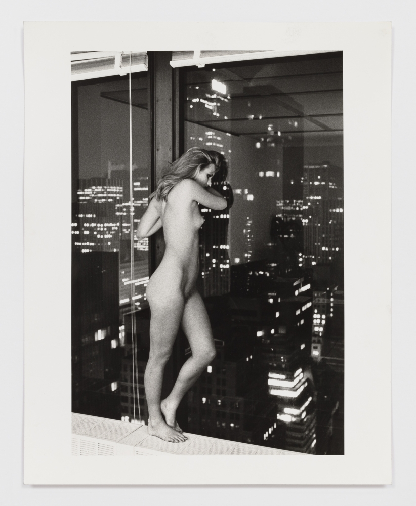 Black and white photographic print of Patti Hansen standing nude and overlooking Manhattan from a window