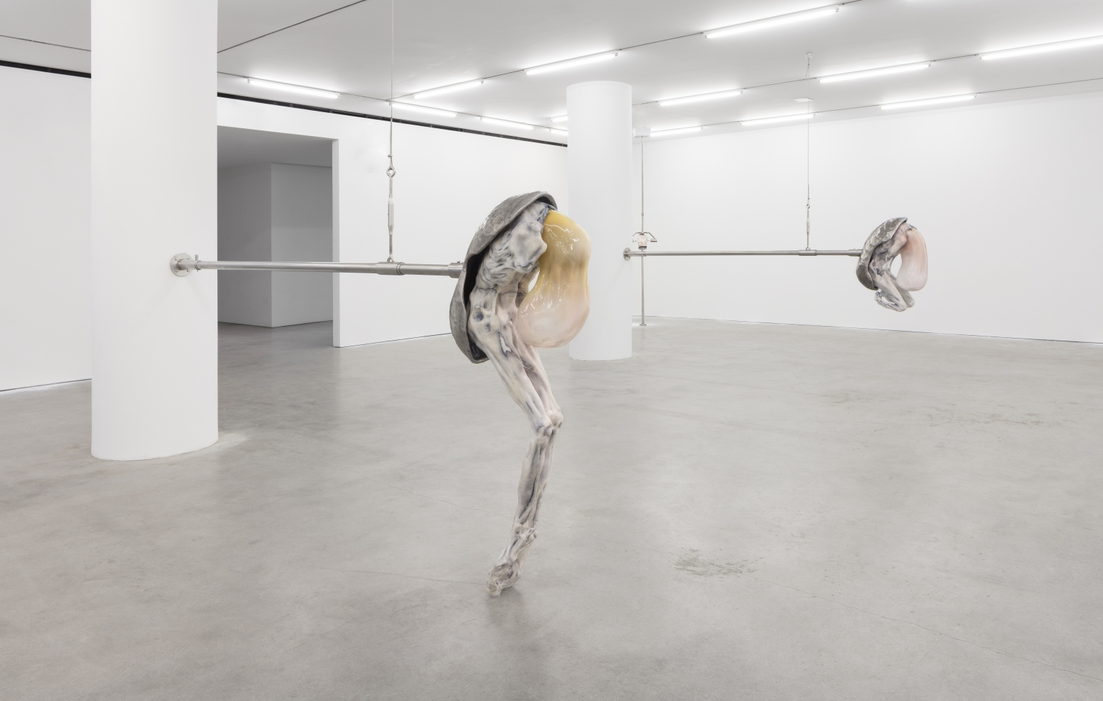 Installation shot of two humanoid figures emerging from oval shell attached by stainless steel rod in an Ivana Bašić exhibition.