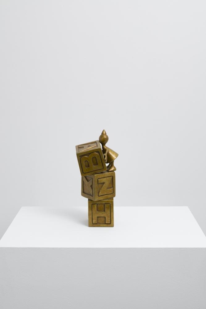 Small bronze sculpture of alphabet blocks by Tom Otterness.