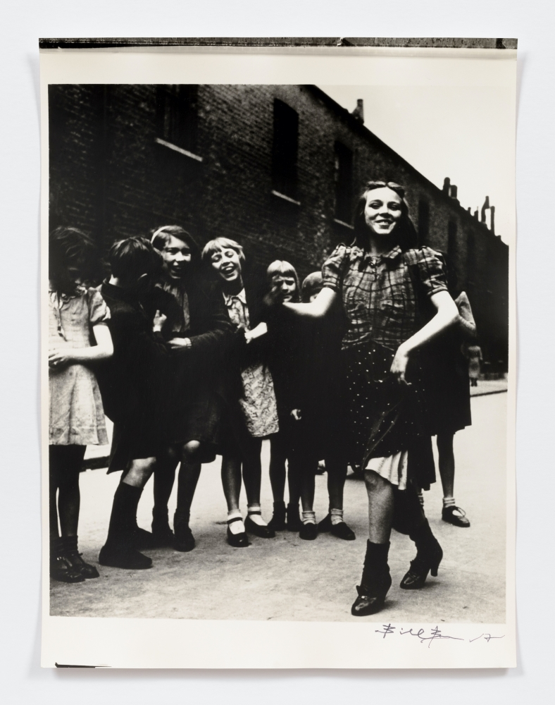 Black and white photographic portrait of girls dancing the Lambeth Walk in the 1930s in front of a dark brick building.