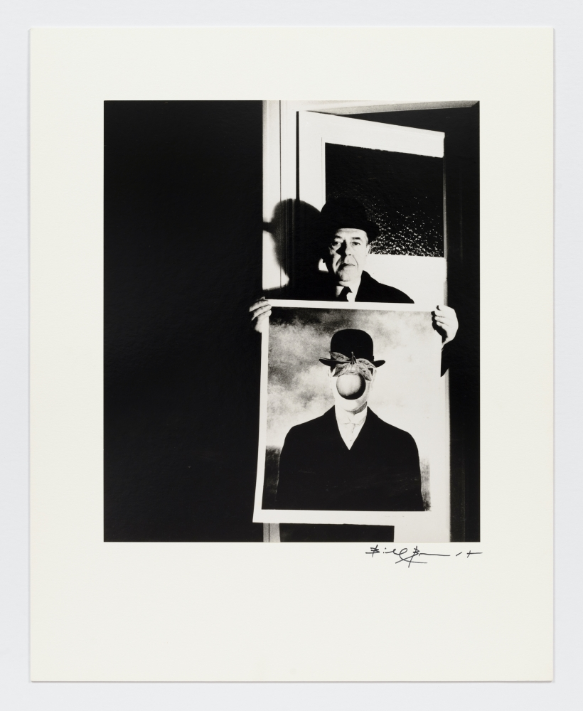 """Black and white photographic portrait of man holding Magritte's """"The Son of Man"""" by Bill Brandt."""